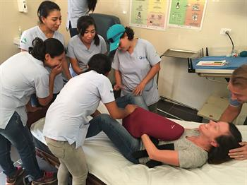 A CU Nursing student simulates going into labor while Guatemalan nurses observe, learn and assist