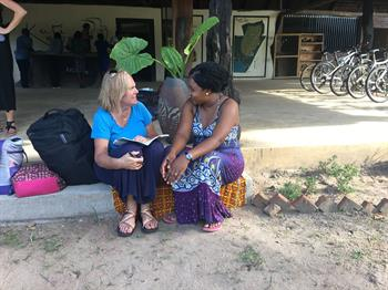 CU Nursing Professor Pam Prag sits on a curb speaking with a Malawian woman
