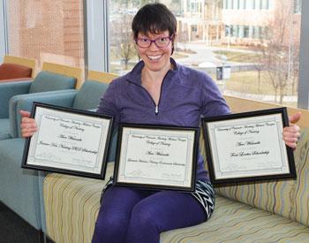 Ann Wislowski holds her three scholarship certificates