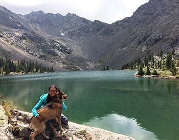 Betzabe Karagozian poses for a photo with her dog in front of a mountain lake