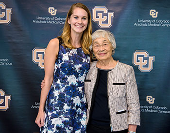 Scholarship Recipient Marissa Yoder poses for a photo with Dr. Furukawa in front of a CU backdrop
